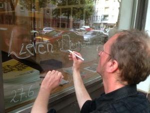 Lieven tekent de openingsuren op het raam van de galerie net voor de opening van de 48 Stunden Neukölln.